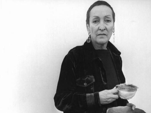 Meret Oppenheim 1975 mit Tasse und Teller mit Pelz überzogen und einem Kohlenobjekt (picture alliance : dpa).jpg