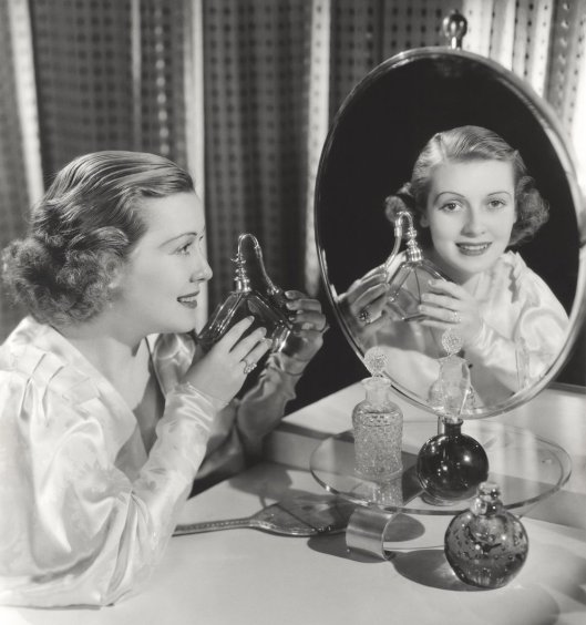Reflection of woman holding perfume atomizer in mirror